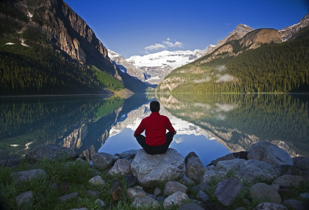 Middle age male meditating on rock at Lake Louise, Alberta, Canada.