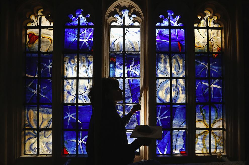 LONDON, ENGLAND - MAY 21: Stained glass artist Helen Whittaker of Barley Studio in York puts finishing touches to one of the new stained glass windows in the 'Lady Chapel' at Westminster Abbey on May 21, 2013 in London, England. The panels, each comprising of more than 50 individual, handmade pieces of glass, are the first to be commissioned by the Abbey for more than a decade. The Abbey has announced plans to unveil the two new stained glass windows, which were designed by British artist, Hughie O'Donoghue, in the Chapel to mark the 60th anniversary of the Coronation of HM The Queen which will take place in the Abbey on June 4, 2013. (Photo by Dan Kitwood/Getty Images) ***BESTPIX***