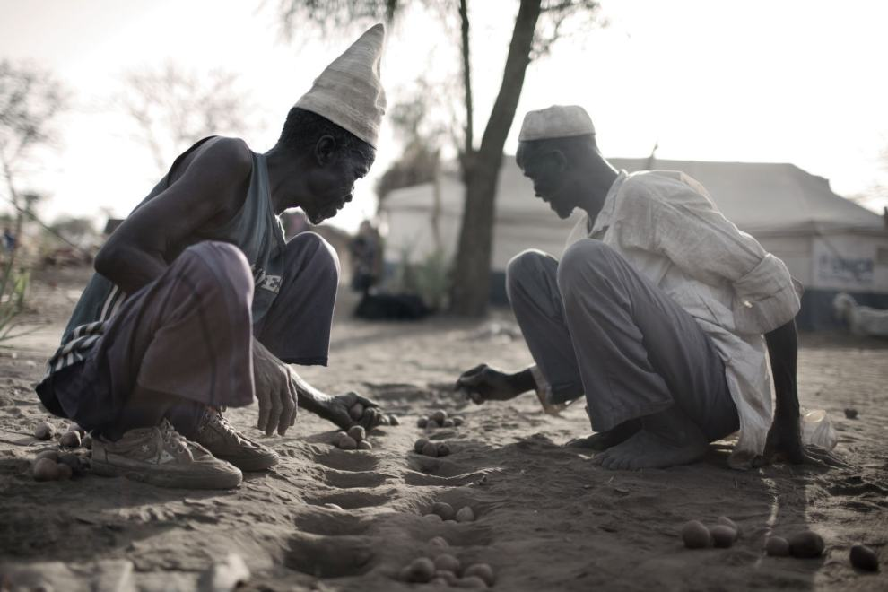 Two elderly men playing a board game on the dusty ground in Doro camp. The men would rather go home to their village and cultivate the fields, than to sit and think of ways to kill time in a refugee camp.