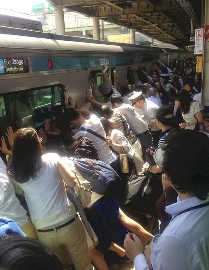 People Working Together To Help A Person Who Got Stuck Between The Platform And A Train