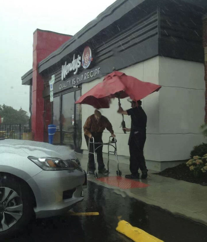 Wendy's Employee Removing Umbrella From A Table Outside To Walk Elderly Gentleman To His Car In The Rain